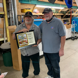 Bob Behrens presenting Butch Sherpen a plaque of apprection for a donation of a side of beef and a whole hog.